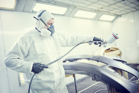 priming paint: Auto repairman mechanic painter in protective workwear and respirator painting car body bumper in paint chamber at garage service station. Toned