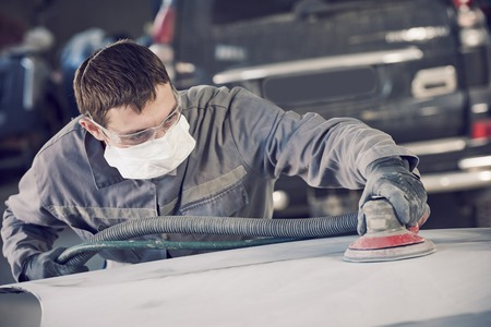 Auto body repairs. Repairman mechanic worker grinding automobile car bonnet by grinder in garage workshop. Toned