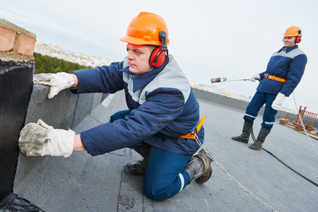 roofer: Flat roof installation. Heating and melting bitumen roofing felt by flame torch at construction site Stock Photo