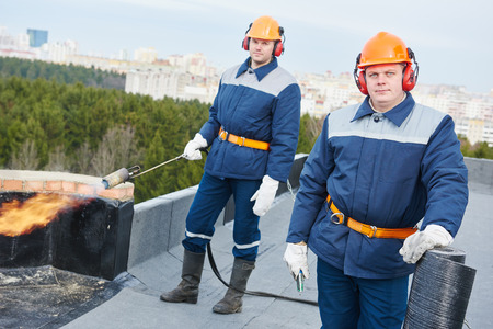 thatcher: Flat roof installation. team of construction workers with bitumen roofing felt and heating and melting flame torch