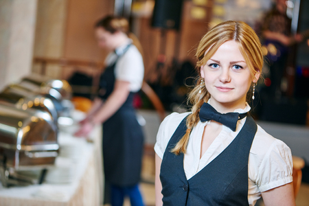 hotel staff: Catering service. Restaurant waitress girl at event. Natural authentic shot in challenging light condition. Stock Photo
