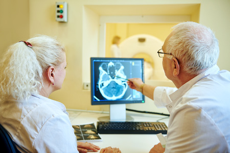 tomography: Computed tomography or MRI scanner test. Team of radiologist woman and man examining x-ray image on digital display Stock Photo