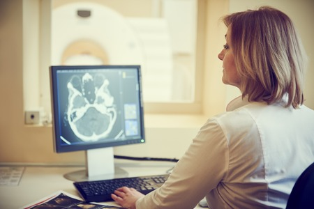 tomography: Computed tomography or MRI scanner test. female radiologist woman examining x-ray image on digital display. Toned