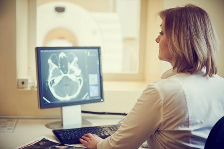 emergencia medica: La tomografía computarizada o una prueba de escáner de resonancia magnética. Mujer radióloga imagen Radiografía de examen en la pantalla digital. tonificado
