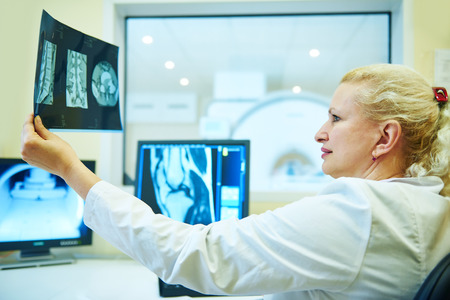 radiologist: Computed tomography or MRI scanner test. female radiologist woman examining x-ray image on digital display. Toned