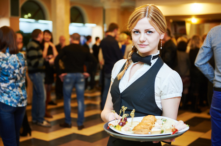 Catering service. Restaurant waitress girl with food tray at event. Natural authentic shot in challenging light condition.