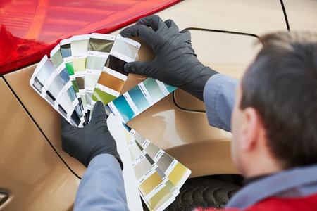 assessment system: auto colour matching. colourist man selecting color of car at automobile repair and renew service station with paint samples