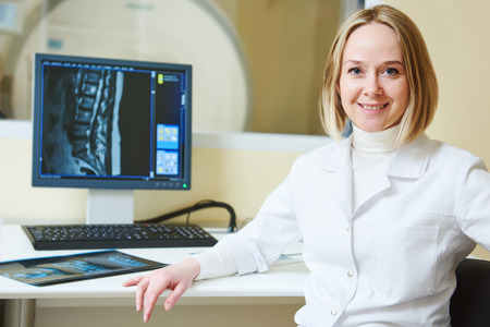 computed: Computed tomography or MRI scanner test. female radiologist woman portrait in front of x-ray image on computer digital display. Stock Photo