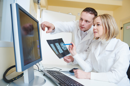 Computed tomography or MRI scanner test. Team of radiologist woman and man examining x-ray image on digital display Imagens