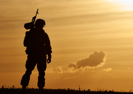 military training: military. soldier silhouette in uniform with machine gun or assault rifle at summer evening sunset