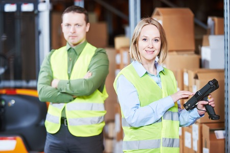 warehousing: Male and female warehousing worker in storehouse with wireless barcode scanner. Warehouse Management System Stock Photo