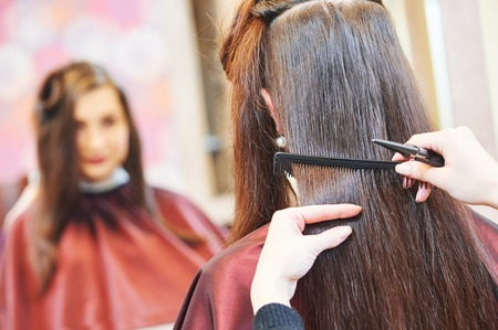 haircutting scissors: Hands of female professional hair stylist with shears and comb during haircutting by hot thermal scissors in hairdresser salon Stock Photo