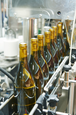 conveyer: bottles with wine on bottling and sealing conveyer production  line at modern winery factory. Shallow DOF.