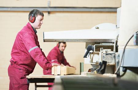 maquinaria: trabajador carpintero industrial con una máquina de sierra circular en el corte transversal de la viga de madera durante la fabricación de muebles Foto de archivo