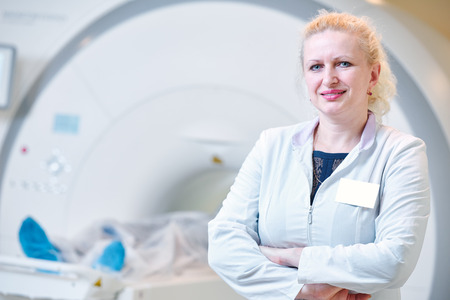 computed: Computed tomography or MRI scanning test. female radiologist woman portrait in front of x-ray radiology equipment Stock Photo