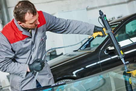Glazier mechanic service worker adding glue on car windshield or windscreen during carglass replacement in automobile workshop garage