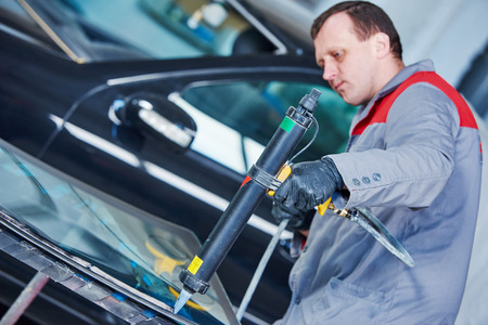 glazier: Glazier mechanic service worker adding glue on car windshield or windscreen during carglass replacement in automobile workshop garage