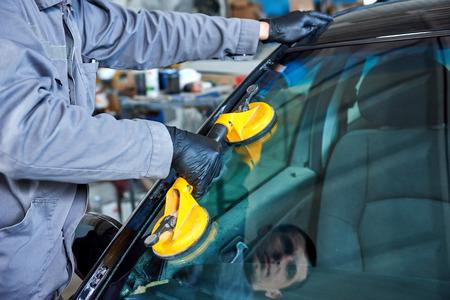 Glazenmaker reparateur mechanic werknemer vervangt windscherm of de voorruit op een auto in de auto-werkplaats garage Stockfoto