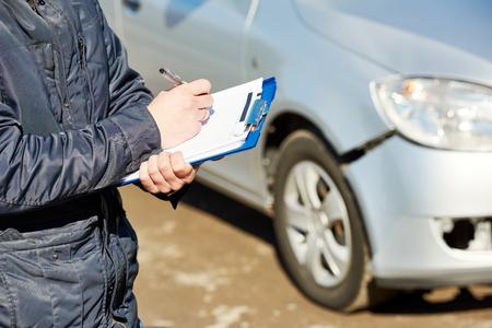 form: Insurance agent recording damage after car crash during  inspecting damaged automobile on claim form Stock Photo
