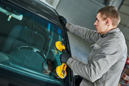 Glazier repairman mechanic worker replaces windshield or windscreen on a car in automobile workshop garage