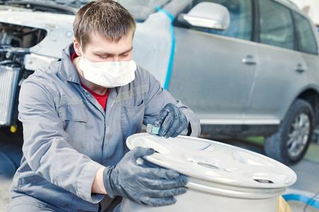 Auto repair mechanic worker with light alloy car wheel disk rim during refurbish at garage service station.