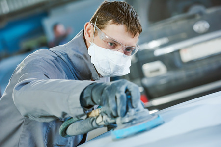 Auto body repairs. Repairman mechanic worker grinding automobile car bonnet by grinder in garage workshop. Toned