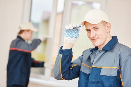 屋内のガラス窓の取付けの前に建設労働者のガラス屋の肖像画 写真素材