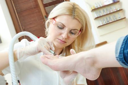 chiropody: Pedicure or chiropody. female manicurist making toe care - polishing feet in beauty salon Stock Photo