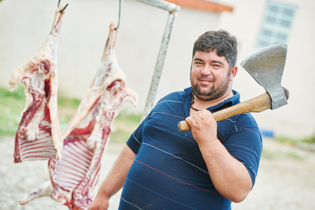 carcass: Real authentic male butcher with axe and sheep carcass meat outdoors