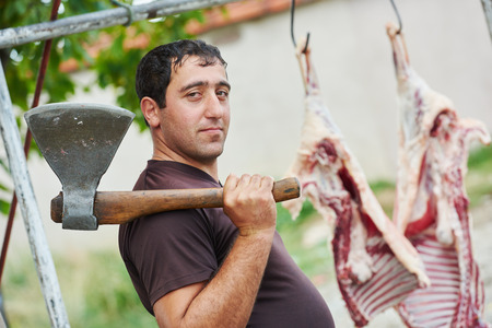 carcass meat: Real authentic male butcher with axe and sheep carcass meat outdoors