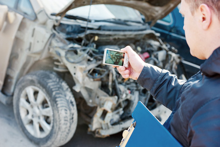 damaged: Insurance agent photographing damage after car crash during  inspecting damaged automobile for claim form
