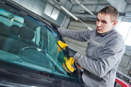 automobile workshop: Glazier repairman mechanic worker replaces windshield or windscreen on a car in automobile workshop garage
