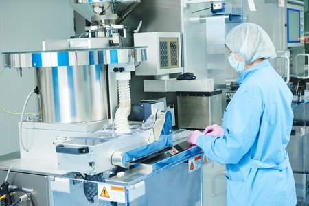 Pharmaceutics. Pharmaceutical industry worker operates blister and cartoning packaging machine at factory Archivio Fotografico