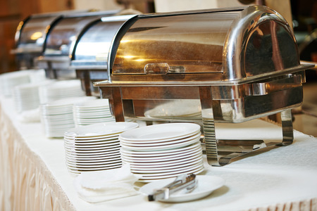catering food: Food catering service. Buffet table with heated steam pans and plates in row