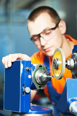 industrial worker sharpen tool with grinding machine at metalworking manufacture factory photo
