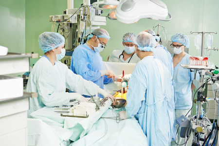 physicals: Team of surgeon in uniform perform heart transplantation operation on a patient at cardiac surgery clinic