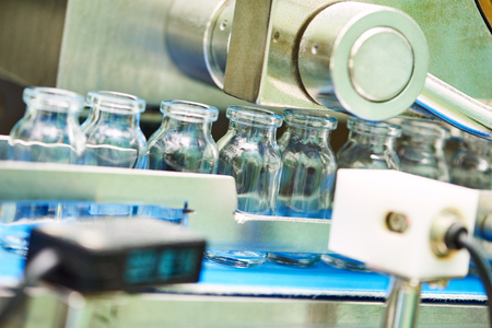 sterility: pharmaceutical industry. Production line machine conveyor with glass bottles ampoules at factory Stock Photo