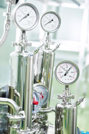 Gros plan des manomètres, tuyaux et robinets vannes de système de chauffage dans une salle de chaudière usine pharmaceutique