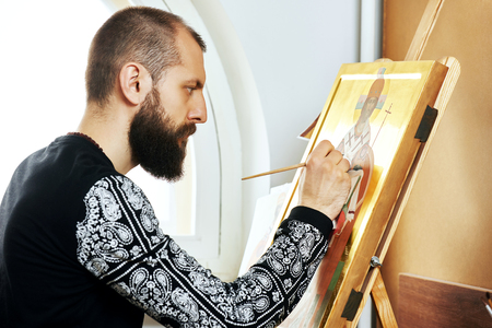 iconography: Iconography. Religious icon painter man paints a new icon with brush at workshop Stock Photo