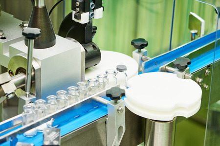 sterility: pharmaceutical industry. Production line machine conveyor at factory with glass bottles ampoules Stock Photo