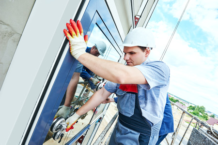 Deux constructeurs travailleurs installant des fenêtres en verre sur la façade du bâtiment d'affaires en utilisant des plaques d'aspiration de verre