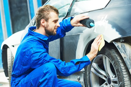 auto mechanic worker applying washing car body preparing for painting at automobile repair and renew service station Reklamní fotografie