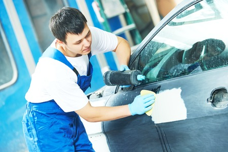 polish: auto mechanic worker applying car polish at automobile repair and renew service station Stock Photo