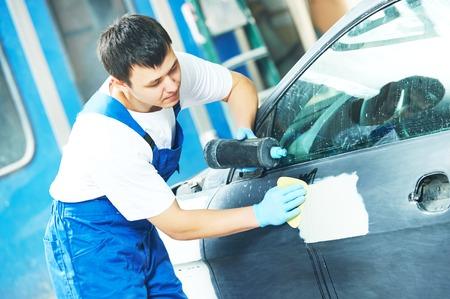 car polish: auto mechanic worker applying car polish at automobile repair and renew service station Stock Photo