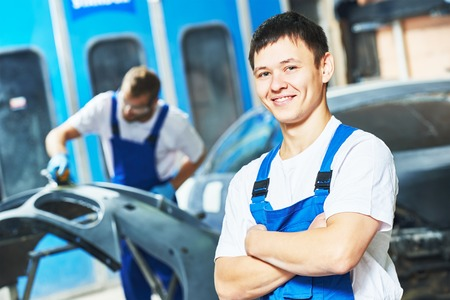 folded hands: Portrait of smiling handsome auto mechanic worker holding hands folded  at automobile repair and renew service station