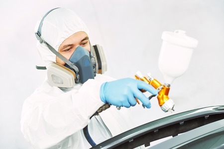 protective workwear: automobile repairman painter in protective workwear and respirator painting car body bumper in chamber