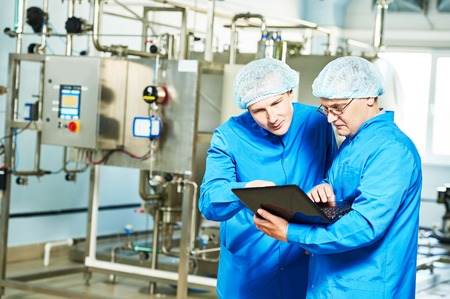 operative: Two pharmaceutical technician male workers in water preparation production line hall at pharmacy industry manufacture factory using notebook computer