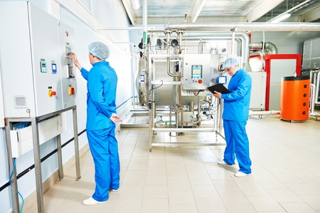 setup operator: Two pharmaceutical male workers operating water preparation production line at pharmacy industry manufacture factory using notebook computer