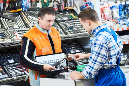 sales assistant: Sales assistant at work. hardware store salesperson demonstrating set of automobile mechanic spanners drill or perforator to buyer customer