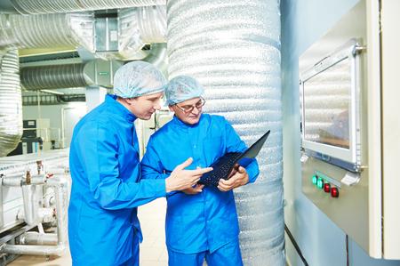 Dos trabajadores de sexo masculino Técnico farmacéutico en el aire acondicionado sala de línea de producción en la industria de la farmacia fábrica de fabricación que usan el ordenador portátil